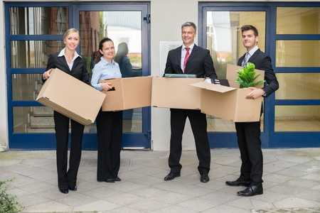 employees holding moving boxes